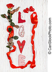 """the word """"love"""" and a red rose with a ribbon lie on white..."""