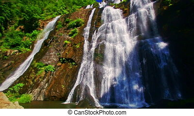 Close View of Waterfall among Forestry Rocky Hills - close...
