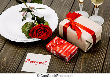 plate with red rose and gift boxes lie on wooden surface