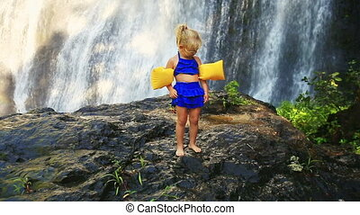 Small Blond Girl Stands on Stone against Large Waterfall