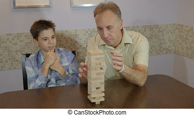 Dad and son playing board game Jenga At home.