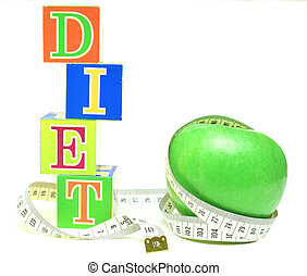 tape measure wrapped around green apple and cubes with...