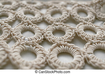Close-up of braided cord pattern rings on white textured...