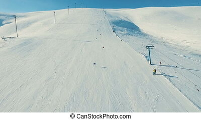 Skiers track by the ski-lift.