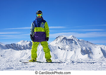 snowboarder standing on the top of a mountain on the...