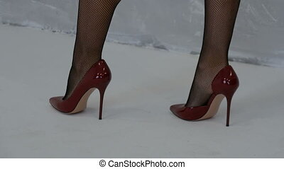 Beautiful female legs in stockings and red high-heeled shoes...