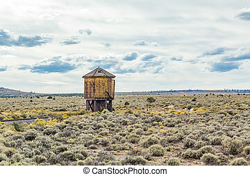 Water Tower - A water tower sits along the tracks of a...