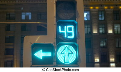 Green arrow. Traffic lights regulate the movement of vehicles. At night in the winter.