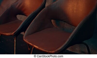 Vintage leather armchairs in the dim light.