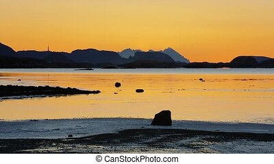 Timelapse of tide and sunset over mountain in a fjord -...