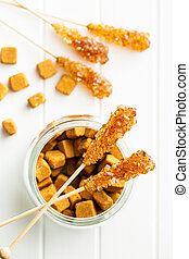 Brown amber sugar crystal on wooden stick. - Brown amber...