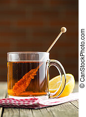 Tea cup with sugar crystal on wooden stick. - Tea cup with...