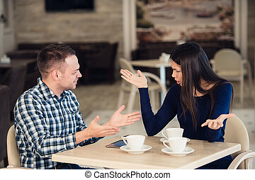 Young couple arguing in a cafe. She's had enough, boyfriend...