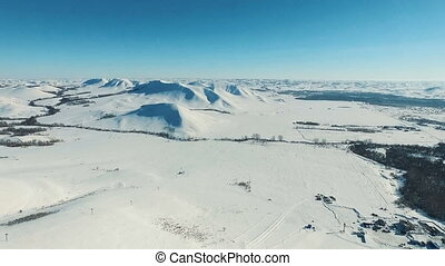 Aerial shot of mountains and fields by ski resort.