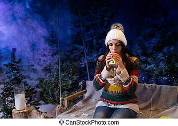 Beautiful young woman drinking hot drink in a snow-covered...