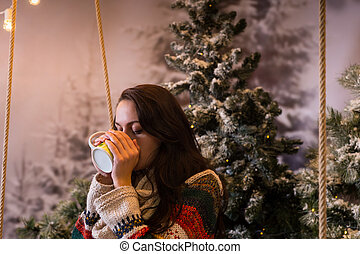 Young woman drinking hot drink from a cup in a snow-covered...