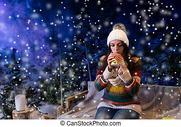 Beautiful woman drinking hot drink in a snow-covered park,...