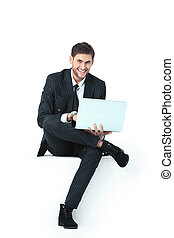handsome young business man sitting on a white modern chair