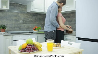 Young couple in the kitchen. drinking tea and eating fruit