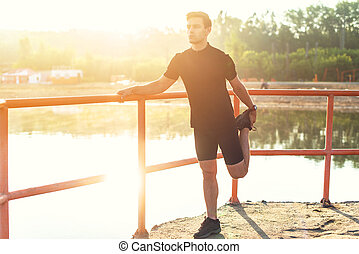 Fit young man preparation for running workout. Jogger...