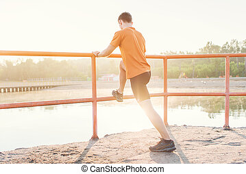 Fitness man stretching his leg muscles outdoors. - Fitness...
