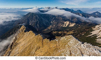 Aerial view above mountain ridge with river of clouds....