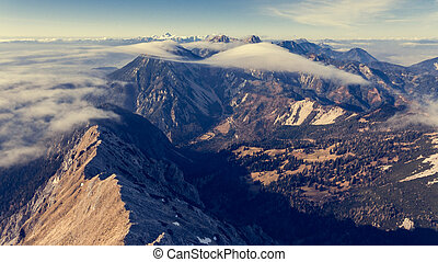 Aerial view above mountain ridge with river of clouds.
