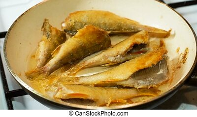 Fish fried in hot oil in a frying pan
