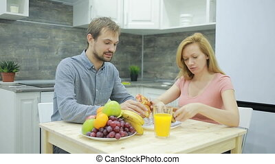 Young couple in the kitchen. drinking tea and eating fruit -...