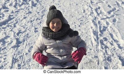 Girl Having Fun on Sledge - Smiling young girl having fun on...