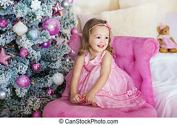 Happy cheerful little girl excited at Christmas Eve, sitting under decorated illuminated  Tree. Greeting card or cover, horizontal with copy space.
