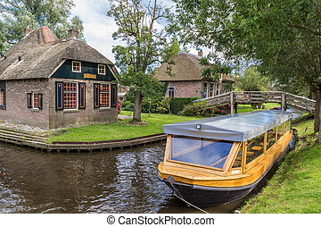 Traditional tourist boat in the canals of Giethoorn,...