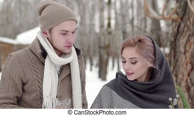 man and woman clink outdoor winter
