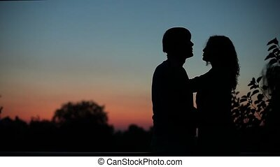 silhouettes of couples kissing at sunset