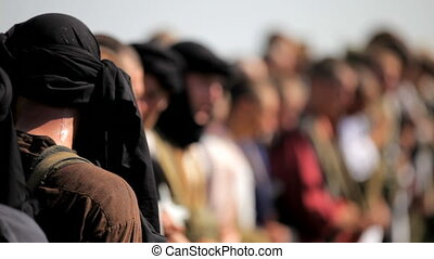 Muslims stand in a row - Dressed in Muslim clothes soldiers.