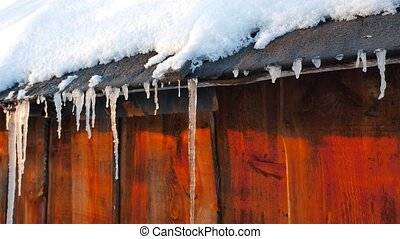 Icicles on the roof of an old barn. Slider. UltraHD (4K)