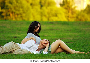 couple laying on park lawn - young couple laying on park...