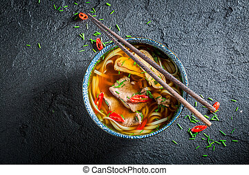 Delicious Red Curry soup in black bowl with chopsticks