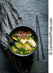 Yummy miso soup with salmon in black bowl