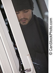 burglar breaks into house - Burglar with crowbar breaks into...