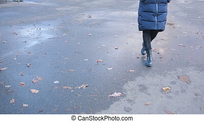 Girl wearing black combat boots splashing in a puddle after...