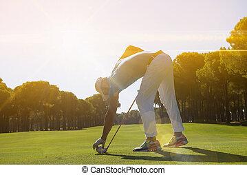 golf player placing ball on tee.
