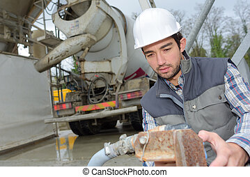 Man holding pipe next to cement lorry