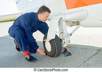 worker checking undercarriage of plane