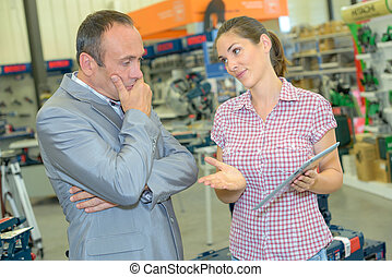 Lady holding tablet, trying to persuade man
