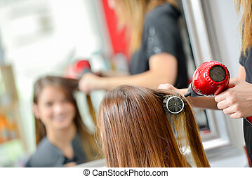 Hair dresser drying a customer's hair