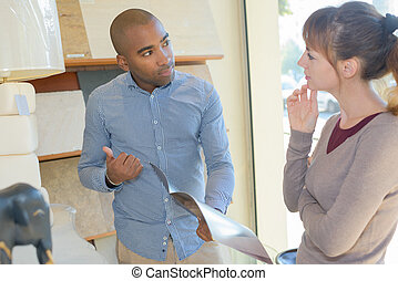 Man and woman looking at catalogue in home furnishings shop