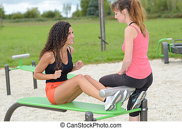 Female friends using outdoor exercise equipment