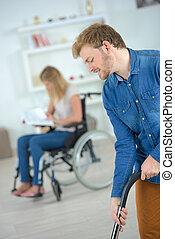 boyfriend helping wheelchair girlfriend to do hoovering