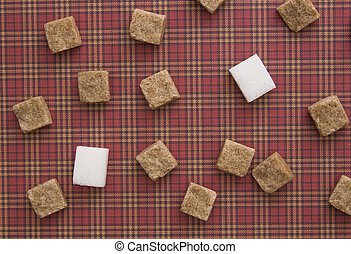 Brown and white sugar cubes on red background. Copy space....